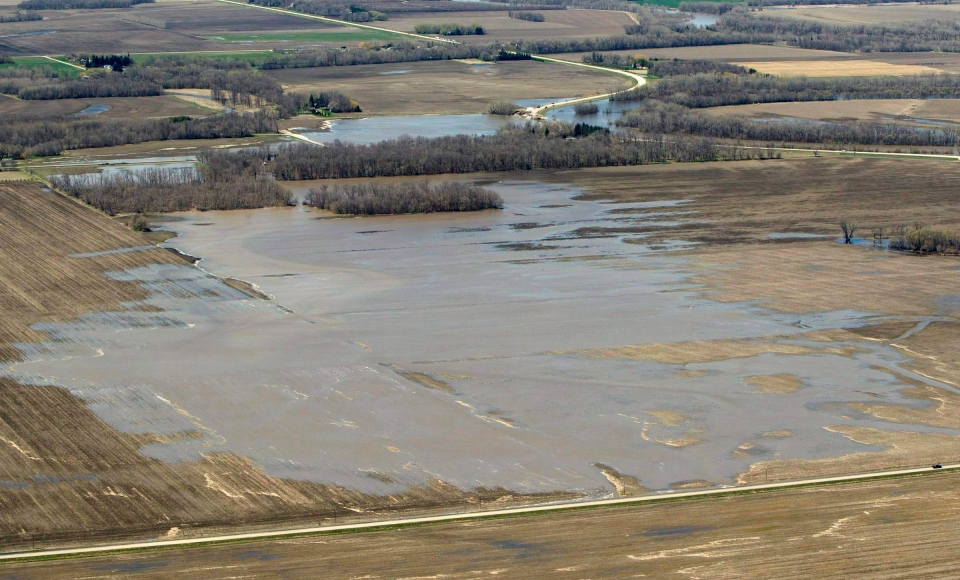 Flood waters from the breach in the dike at the hoop and holler bend fans out from the Assiniboine River, top of frame, to surrounding fields outside of Portage La Prairie, Man., on May 14, 2011. (Jonathan Hayward / THE CANADIAN PRESS)