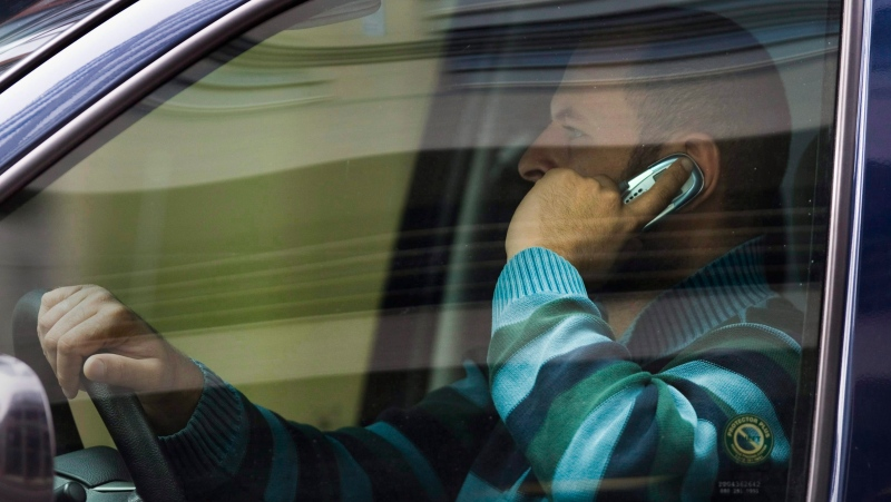 A driver talks on his cell phone while driving in downtown Ottawa on Wednesday, Sept. 30, 2009. (The Canadian Press/Sean Kilpatrick)
