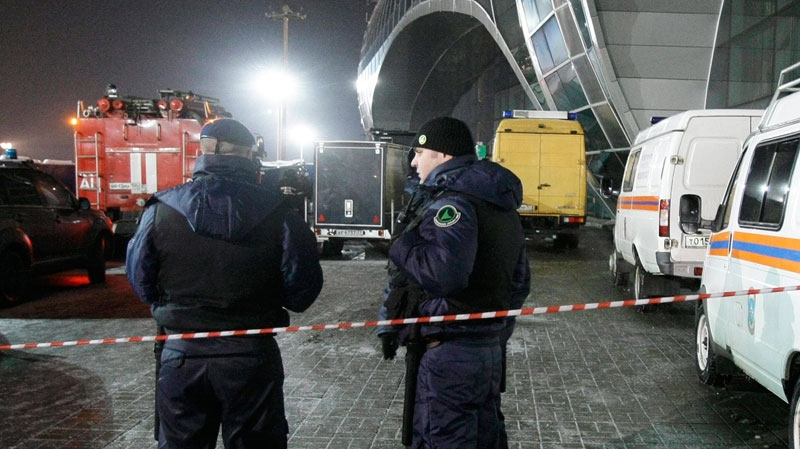 Airport security guards stand after a blast at Domodedovo airport in Moscow, Monday, Jan. 24, 2011. (AP / Misha Japaridze)