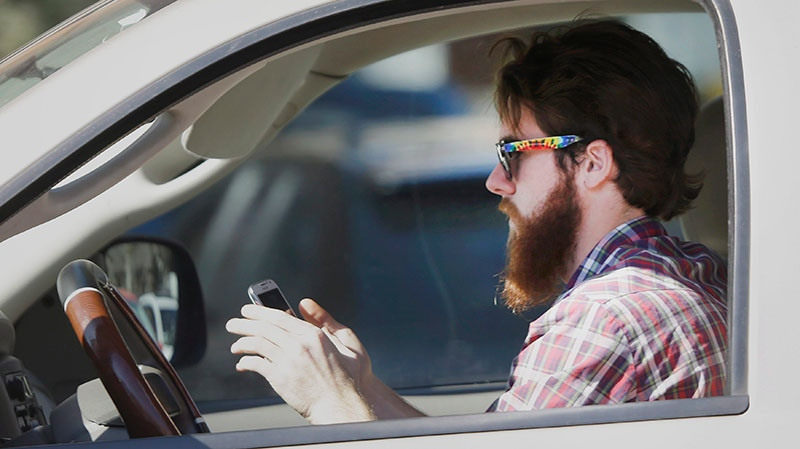 An man works his phone as he drives through traffic in Dallas, Tuesday, Feb. 26, 2013. Texas lawmakers are considering a statewide ban on texting while driving. (AP / LM Otero)
