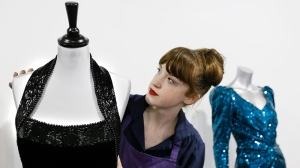 The beaded neckline of a Catherine Walker black velvet evening gown worn for a Vanity Fair photo shoot by Britain's Princess Diana is adjusted by house assistant Lucy Bishop at the Kerry Taylor auction rooms in London, Thursday, Feb. 28, 2013. (AP / Kirsty Wigglesworth)