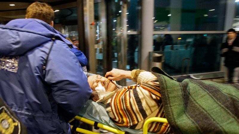 A man wounded in a blast is carried away at Domodedovo airport in Moscow, Monday, Jan. 24, 2011.  (AP / Ivan Sekretarev)