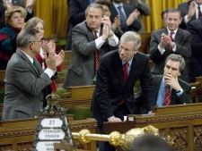 Opposition leader Stephane Dion recieves a standing ovation from some caucus members after voting down a bill to extend the anti-terrorism act, as Deputy leader Michael Ignatieff remains sitting, on Parliament Hill in Ottawa on Tuesday Feb. 27, 2007. (CP / Tom Hanson)
