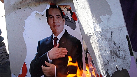 Protestors burn a photo of former Tunisian President Zine El Abidine Ben Ali during a demonstration in Tunis, Monday, Jan. 24. 2011. The protesters are angry that holdovers from former President Zine El Abidine Ben Ali's regime hold leading posts in the interim government in place since last week.