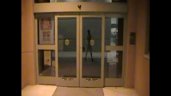 In this image taken from a YouTube video posted by Jared Lee Loughner and released by Pima Community College to the Associated Press, a campus books station is shown at Pima Community College, with the reflection of Loughner in Tucson, Ariz. The video shot by the suspected gunman in the attack on Rep. Gabrielle Giffords and others showed the former community college student touring campus at night and at times rambling about free speech and the Constitution. (AP / Pima Community College)
