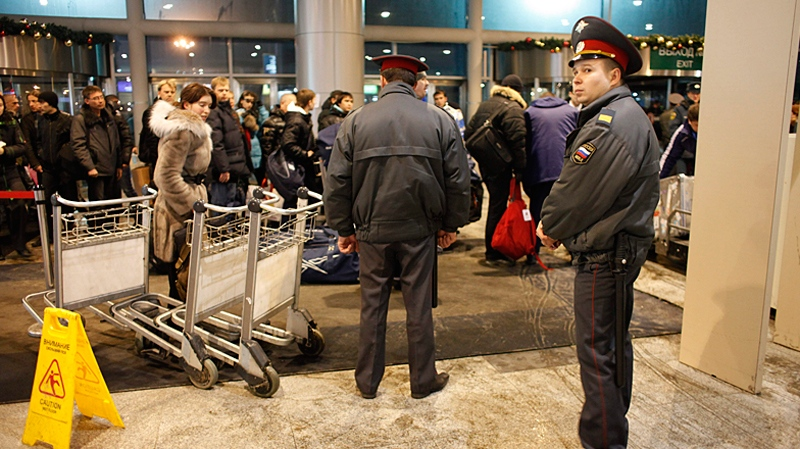 Russian police officers stand in guard as passengers queue to pass through a security check following a blast, at Domodedovo airport in Moscow, late Monday, Jan. 24, 2011. (AP / Alexander Zemlianichenko)