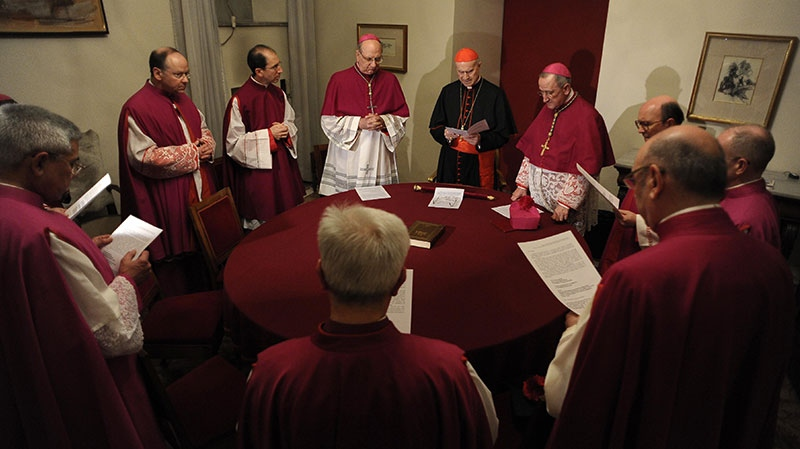 Cardinal Tarcisio Bertone, Vatican Secretary of State, at center with red skull cap, officially takes over the vacant See as camerlengo, chamberlain, before sealing Pope Benedict XVI's apartment, after Benedict left the Vatican, Thursday, Feb. 28, 2013. (L'Osservatore Romano)