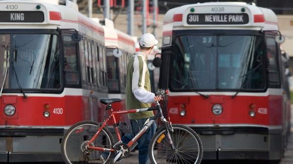 A cyclist walks past TTC streetcars in Toronto, Saturday, April 26, 2008. (Adrian Wyld / THE CANADIAN PRESS)