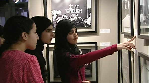 Students look at photos on display at Living Together exhibit (Jan. 25, 2011)