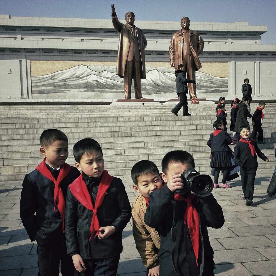 In this photo taken with an iPhone and posted to Instagram, North Korean school boys play with an Associated Press photographer's professional camera in front of statues of the late leaders Kim Il Sung and Kim Jong Il, on Mansu Hill in Pyongyang, North Korea, Feb. 16, 2013. (AP / David Guttenfelder)