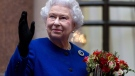 Queen Elizabeth II looking up and waving to members of staff of The Foreign and Commonwealth Office as she ended an official visit, part of her Jubilee celebrations in London, Tuesday, Dec. 18, 2012. (AP / Alastair Grant)