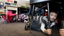 Grade 1 student, six-year-old Joseph Kim, takes cover under his desk during an earthquake drill at Hollyburn Elementary School in West Vancouver, B.C., on Wednesday January 26, 2011. (Darryl Dyck / THE CANADIAN PRESS)