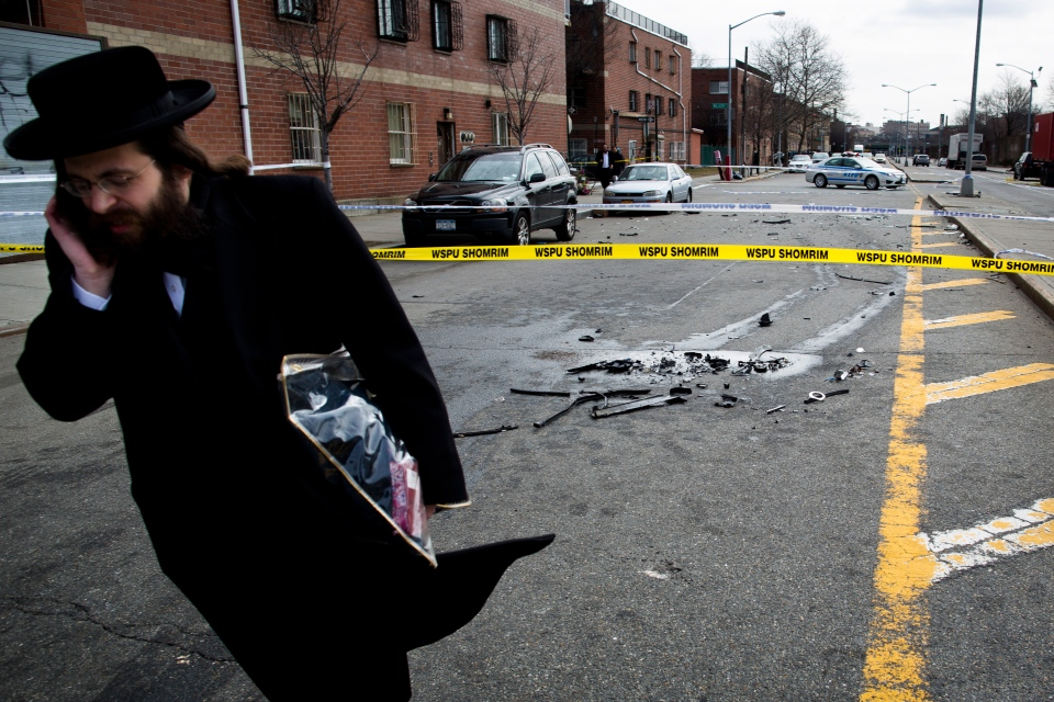 A man walks past debris from a fatal accident that claimed the lives of two expectant parents on their way to the hospital, in the Brooklyn borough of New York, Sunday, March 3, 2013, . (AP / John Minchillo)