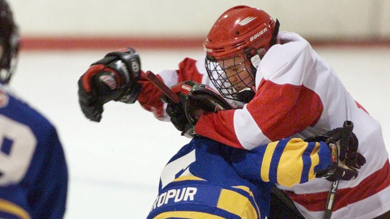 "A player from the Dartmouth Whalers collides with a member of the Cole Harbour Red Wings, in peewee ""A"" action in Halifax. (Andrew Vaughan / THE CANADIAN PRESS)"