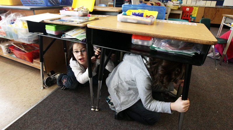 Grade two students Emily McMyn, left, and Maggie Kita take cover under their desks during an earthquake drill at Hollyburn Elementary School in West Vancouver, B.C., on Wednesday Jan. 26, 2011. (Darryl Dyck / CANADIAN PRESS)