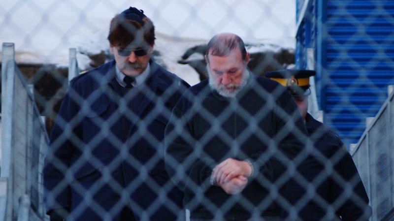 Catholic priest Eric Dejaeger is escorted by police outside an Iqaluit, Nunavut courtroom Jan. 20, 2011 after his first appearance for six child sexual abuse charges in Igloolik dating back to the 1970s. (Chris Windeyer / THE CANADIAN PRESS)