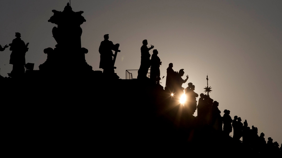 The sun sets behind the statues on top of the Bernini colonnade in St. Peter Square, at the Vatican, Monday, March 4, 2013. (AP / Andrew Medichini)