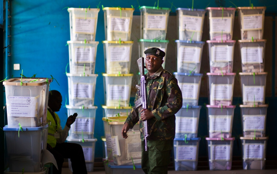 An officer helps to carry ballot boxes for stacking after their results were tallied, at a vote tallying center in Nairobi, Kenya on March 5, 2013. (AP Photo/Ben Curtis)