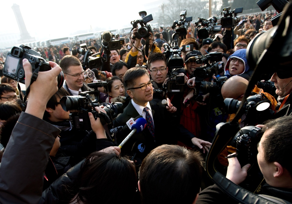 U.S. Ambassador to China Gary Locke, centre, is mobbed by journalists as he attends the opening session of the annual National People's Congress at the Great Hall of the People in Beijing, Tuesday, March 5, 2013. (AP / Andy Wong)