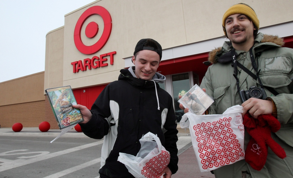 First customers Scott Lester, left, and Sam Skelhorn, exit the new Target store with their purchases in Guelph, Ont. on Tuesday, March 5, 2013. (Dave Chidley / THE CANADIAN PRESS)