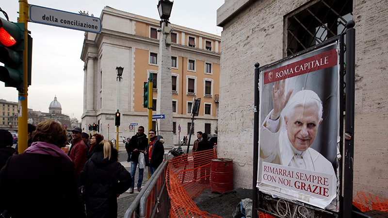People walk past a poster of Pope Benedict XVI reading :