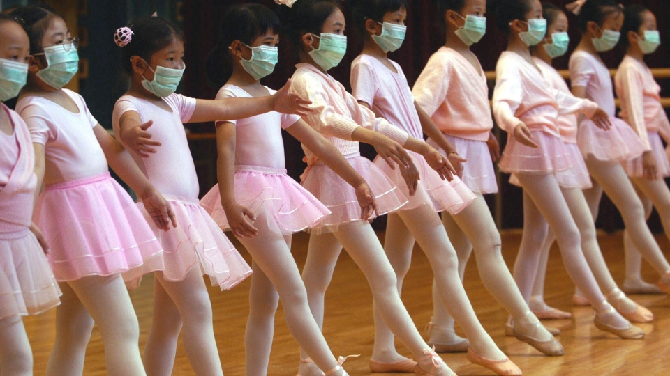Children attend ballet lessons wearing masks to protect themselves from severe acute respiratory syndrome, SARS, in Hong Kong, in this April 27, 2003 file photo. (AP / Vincent Yu)