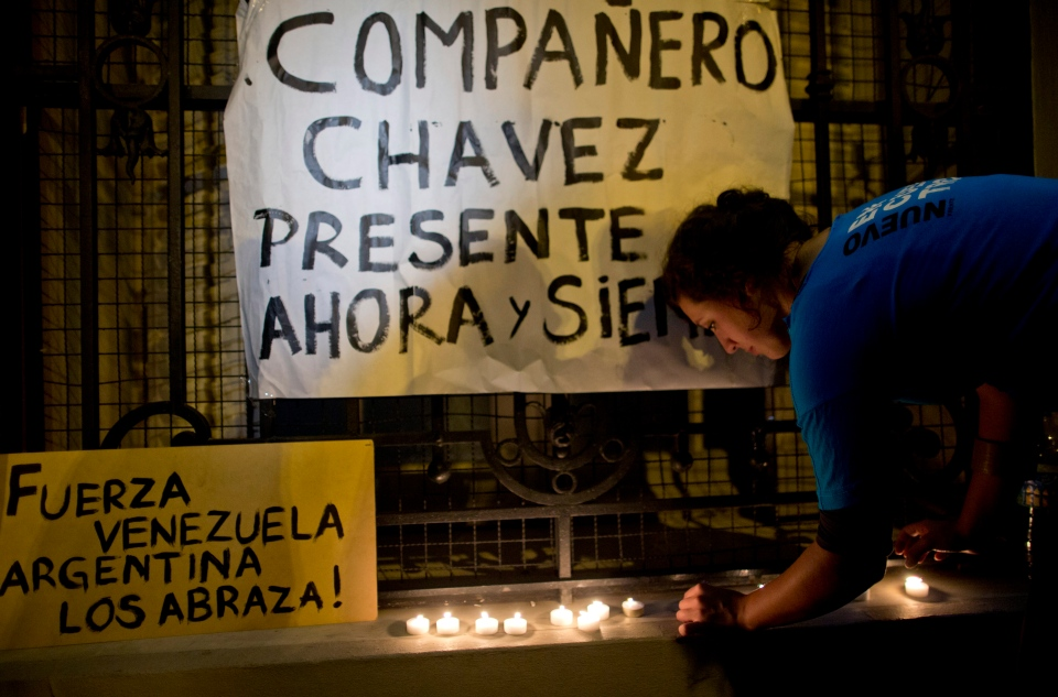 An Argentine supporter of Venezuela's President Hugo Chavez places a candle near signs reading in Spanish