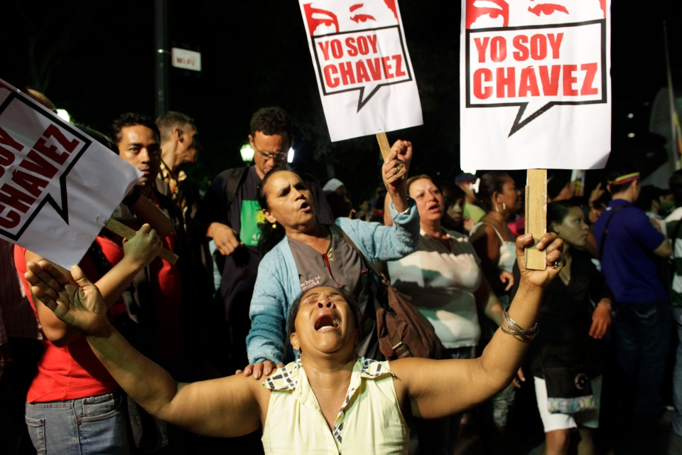 """A supporter of Venezuela's President Hugo Chavez cries as she holds a sign that reads in Spanish """"I am Chavez"""" as Chavistas gather in Bolivar square to mourn Chavez's death in Caracas, Venezuela, Tuesday, March 5, 2013. (AP / Ariana Cubillos)"""