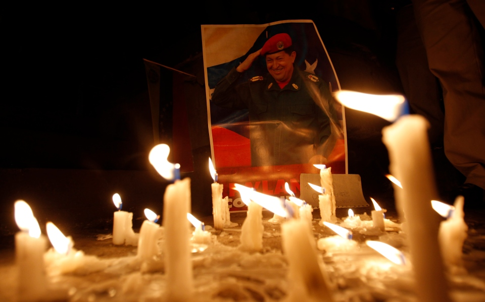 Candles, placed by mourner demonstrators, burn in front of an image of Venezuela's President Hugo Chavez outside Venezuela's embassy in Quito, Ecuador, Tuesday, March 5, 2013. (AP / Dolores Ochoa)