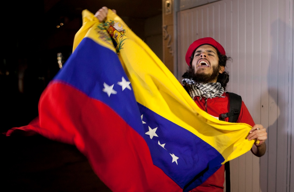 A Mexican supporter of Venezuela's President Hugo Chavez waves a Venezuelan flag in front of Venezuela's embassy in Mexico City, Tuesday, March 5, 2013. (AP / Eduardo Verdugo)