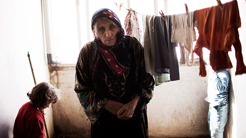 A Syrian woman is seen at an abandoned building where several families took refuge due to fighting between Free Syrian Army fighters and government forces in the northeastern city of Qamishli, Syria, Thursday, Feb. 28, 2013. (AP / Manu Brabo)