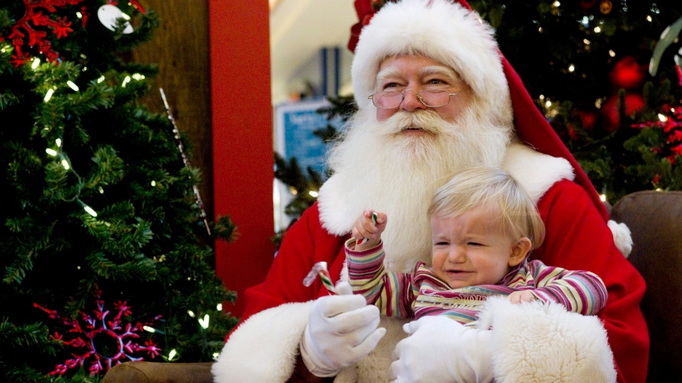 Seventeen-month-old Siria Pirone reacts as she sits with a Santa Claus for a photo at a mall in Toronto on Friday, Dec. 10, 2010. (Chris Young / THE CANADIAN PRESS)