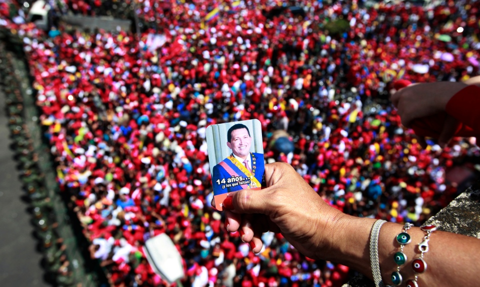 A supporter of Venezuela's late President Hugo Chavez holds a picture of him above a crowd waiting for Chavez's coffin in Caracas, Venezuela, Wednesday, March 6, 2013. (AP / Ricardo Mazalan)