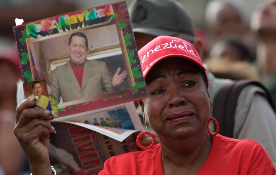 A woman holds a picture of President Hugo Chavez outside the military hospital where he died Tuesday in Caracas, Venezuela, Wednesday, March 6, 2013. (AP / Ariana Cubillos)