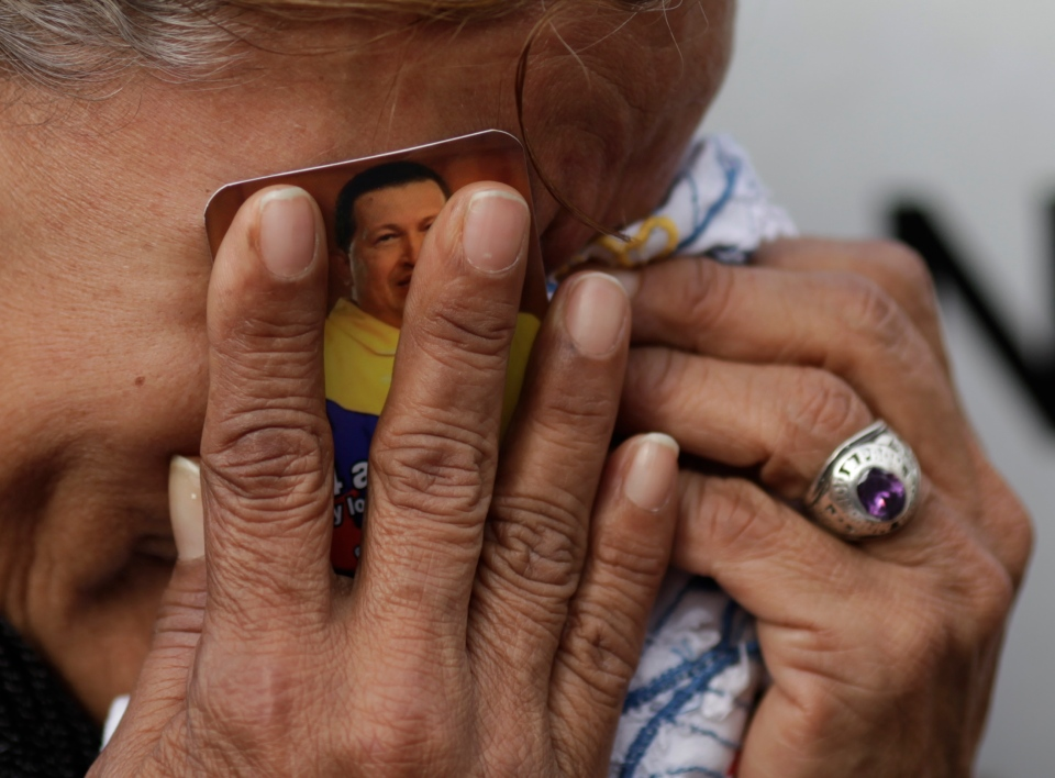 A woman holds a picture of President Hugo Chavez against her face as she cries outside the military hospital where he died Tuesday in Caracas, Venezuela, Wednesday, March 6, 2013. (AP / Ariana Cubillos)