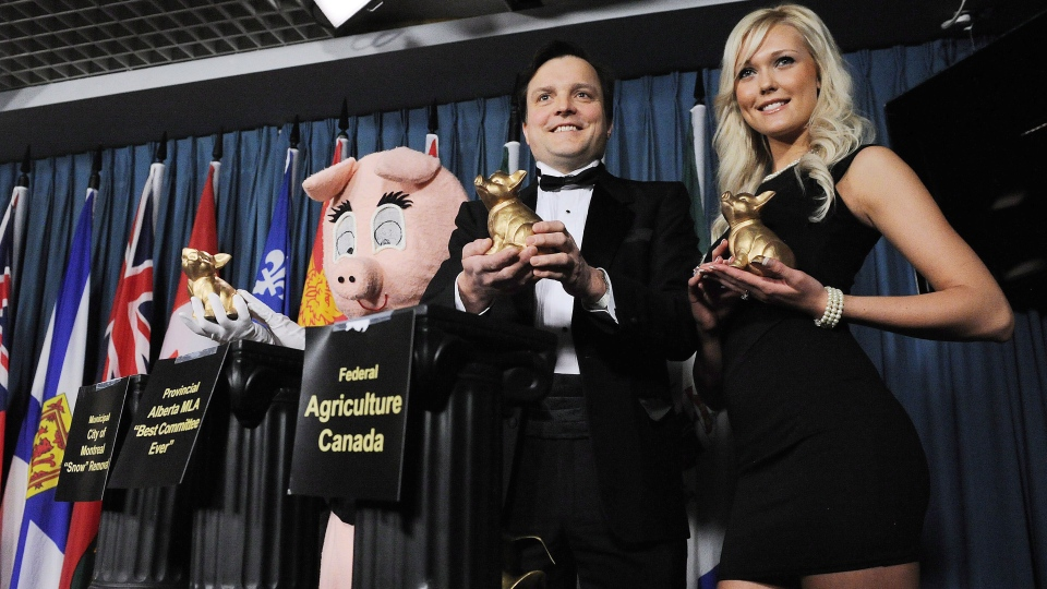 Porky the Waste Hater, Canadian Taxpayers Federation federal director Gregory Thomas and Catherine Briere present the 14th annual Teddy Waste Awards on Parliament Hill in Ottawa on Wednesday, March 7, 2012.  (Sean Kilpatrick  / THE CANADIAN PRESS)