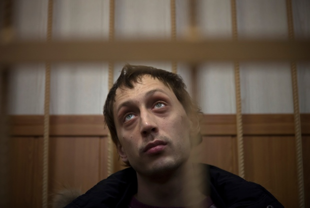 Bolshoi soloist Pavel Dmitrichenko listens in a courtroom in Moscow, Russia, Thursday, March 7, 2013. (AP Photo/Alexander Zemlianichenko)