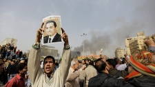 An Egyptian anti-government protester holds a defaced poster of Egyptian President Hosni Mubarak, with the words 'Mubarak, get out' written above, during a demonstration in Cairo, Egypt, Saturday, Jan. 29, 2011. (AP / Ben Curtis)