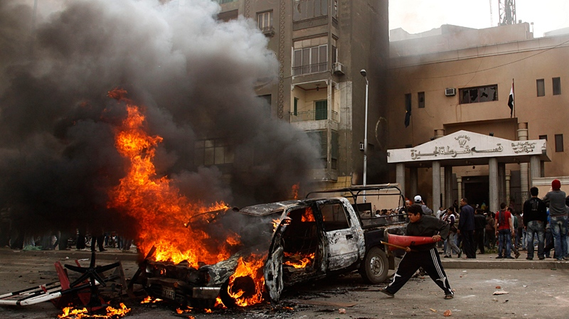 An Egyptian anti-government protester throws a traffic cone into a burning car in front of a burning police station near the pyramids, in Giza, Egypt, Saturday, Jan. 29, 2011. (AP / Victoria Hazou)