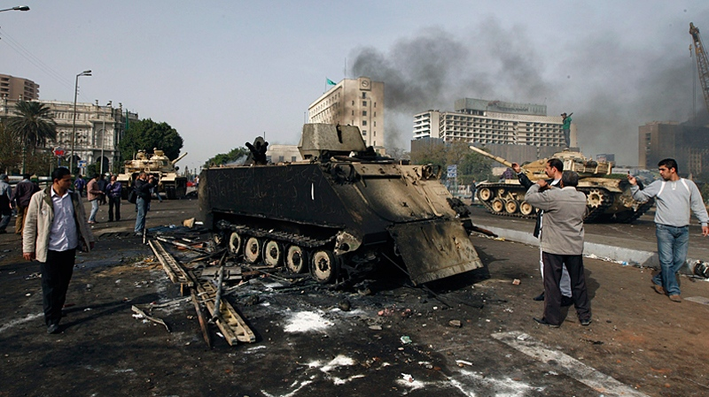 Egyptians photograph a burned out army armored personnel carrier in downtown Cairo, Egypt, Saturday, Jan. 29, 2011. (AP / Halil Hamra)