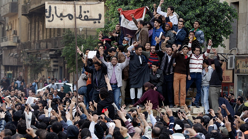 Egyptian anti-government protesters climb atop an Egyptian army armored personnel carrier, next to a signpost bearing the words 'Down Mubarak', in Cairo, Egypt, Saturday, Jan. 29, 2011. (AP / Ben Curtis)