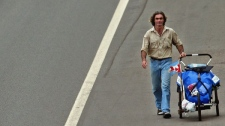 Jean Beliveau walks down a highway near Lujan, some 70 kilometres northwest Buenos Aires, Argentina Monday, March 10, 2003. Beliveau left his home near Montreal on his 45th birthday on Aug. 18 of 2000.