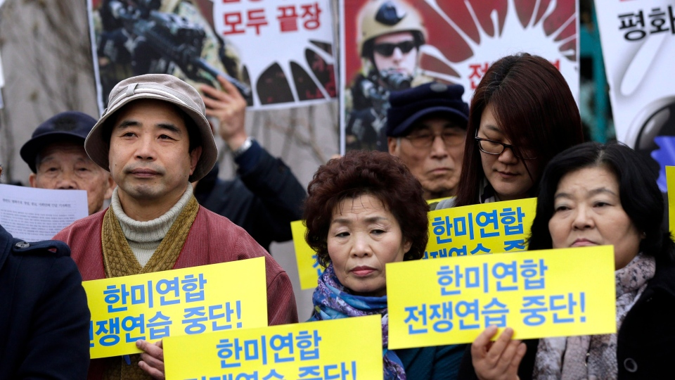 South Korean protesters hold signs during a press conference denouncing the annual joint military exercises, dubbed Key Resolve and Foal Eagle, between South Korea and the United States, in front of the Government House in Seoul, South Korea, Thursday, March 7, 2013. (AP / Lee Jin-man)