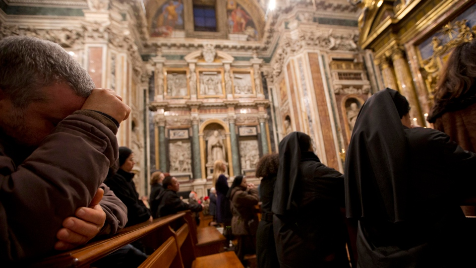 Faithful and nuns pray during a Mass for the election of the pope, in Rome's Saint Mary Major Basilica, Thursday, March 7, 2013. (AP / Andrew Medichini)