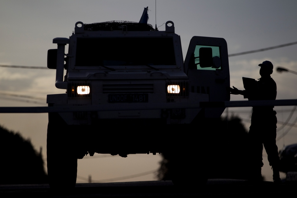A UN peacekeeper checks an armoured vehicle as it leaves from the UNDOF Ziouani camp to cross to Syria at the Quneitra Crossing between Syria and the Israeli-controlled Golan Heights on March 8, 2013. (AP / Ariel Schalit)
