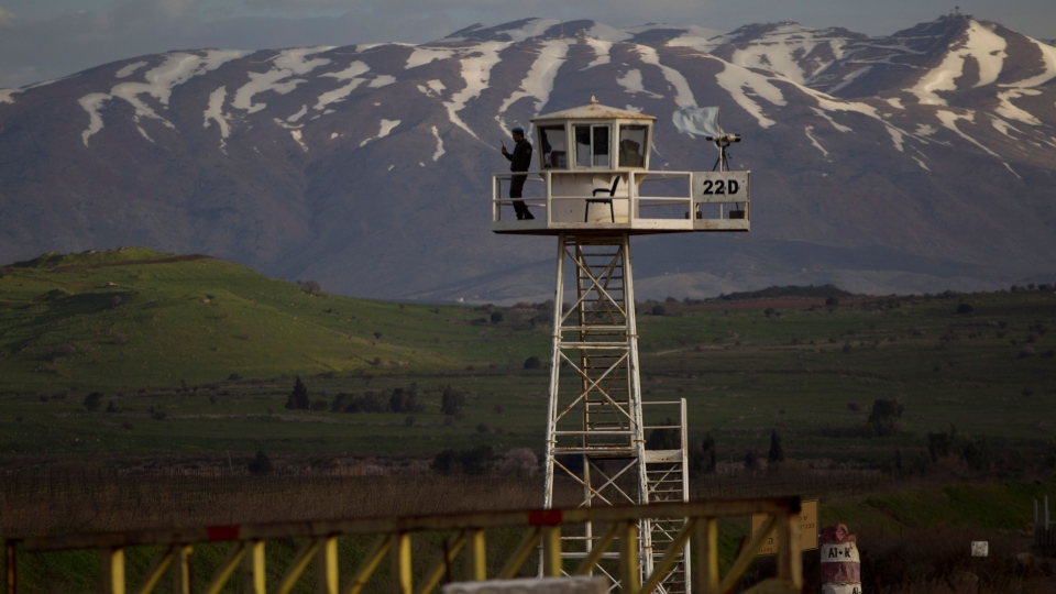 A UN peacekeeper from the UNDOF force stands guard on a watch tower at the Quneitra Crossing between Syria and the Israeli-controlled Golan Heights, Friday, March 8, 2013. (AP / Ariel Schalit)