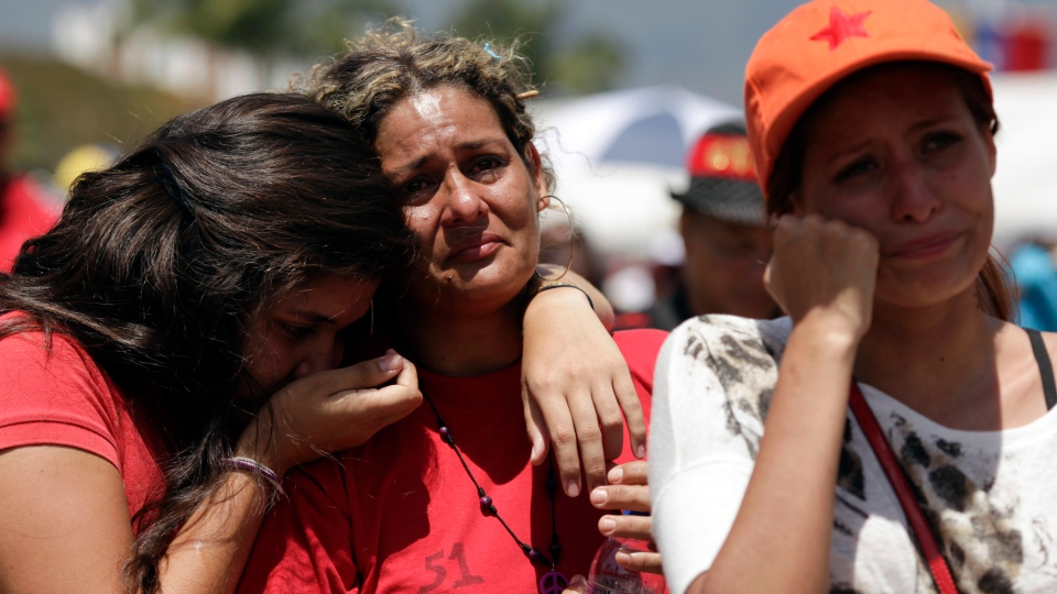 Women cry as they watch on a giant screen the funeral ceremony for Venezuela's late President Hugo Chavez outside the military academy in Caracas, Venezuela, early Friday, March 8, 2013. (AP Photo / Ariana Cubillos)