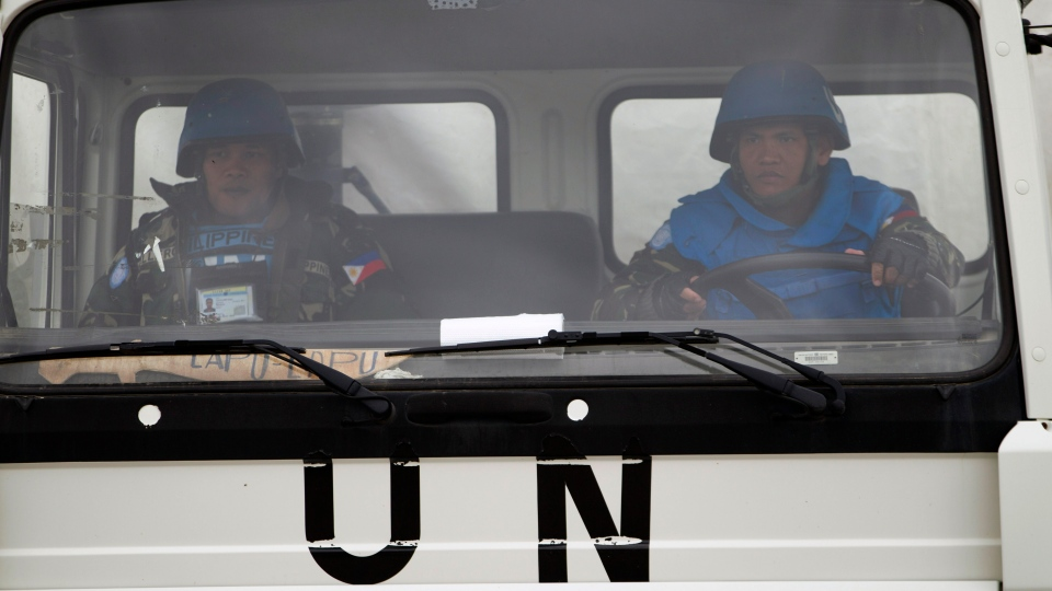 A U.N. peacekeeper from the Philippines drives a UNDOF vehicle as it leaves the Ziouani camp to cross into Syria at the Quneitra Crossing between Syria and the Israeli-controlled Golan Heights, Friday, March 8, 2013. (AP Photo / Ariel Schalit)