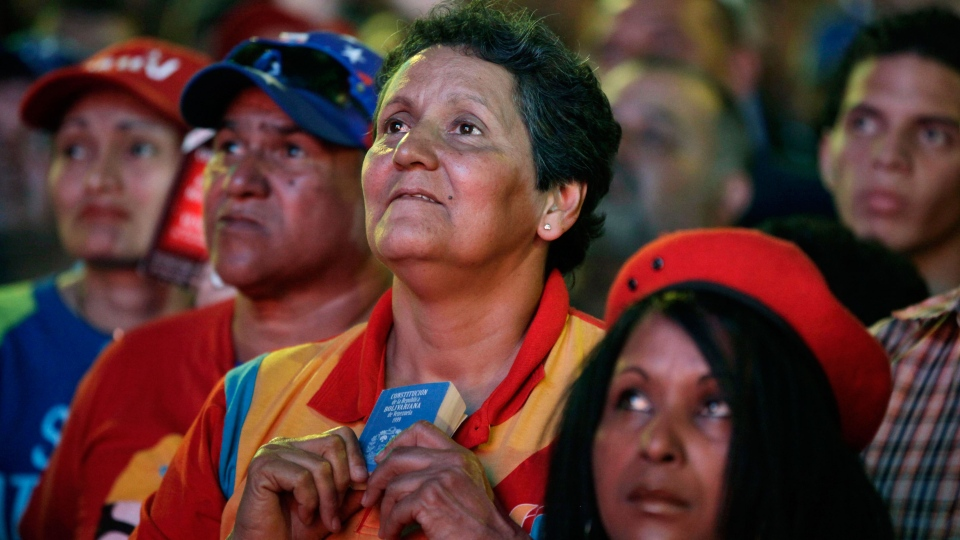 Supporters of Nicolas Maduro watch on a giant screen outside the National Assembly the ceremony in which he is sworn in as Venezuela's acting president in Caracas, Venezuela, Friday, March 8, 2013. (AP / Ariana Cubillos)