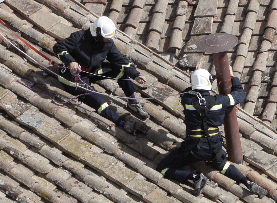 Firefighters place the chimney on the roof of the Sistine Chapel, where cardinals will gather to elect the new pope, at the Vatican, Saturday, March 9, 2013.  (AP / Stringer)